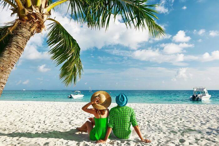 A couple on a beach enjoying a happy summer